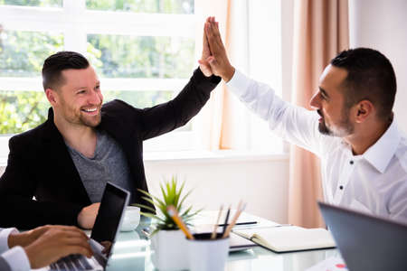 Two Smiling Young Businessmen Giving High Five In Office