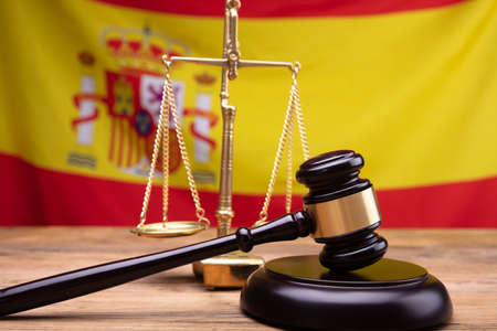Close-up Of Wooden Gavel And Justice Scale In Front Of Spain Flag Фото со стока