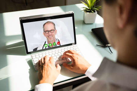 Businessmans hand videoconferencing with happy doctor on laptop
