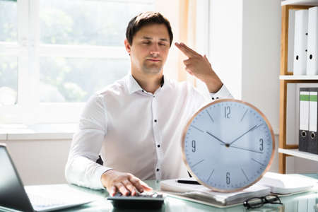 Tired young businessman making shooting gesture behind clock in office
