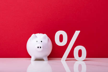 White Piggybank And Percentage Symbol Against Red Wall Stock fotó