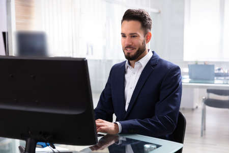 Smiling Young Businessman Using Computer In Office 写真素材