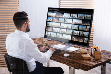Young Male Photo Editor Recherche de photos sur ordinateur au bureau
