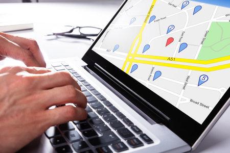 Una persona que usa el mapa GPS con puntero de navegación en la computadora portátil