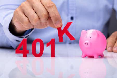 A Person Picking K Alphabet From 401k Pension Plan Beside Piggybank