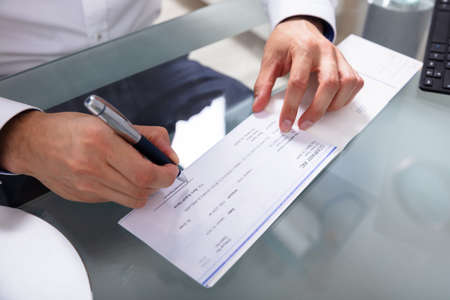 Businessman's Hand Signing Cheque On Glass Desk Stockfoto