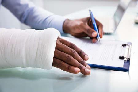 Vue de dessus de l'homme blessé avec un bandage remplissant le formulaire de réclamation d'assurance sur le presse-papiers