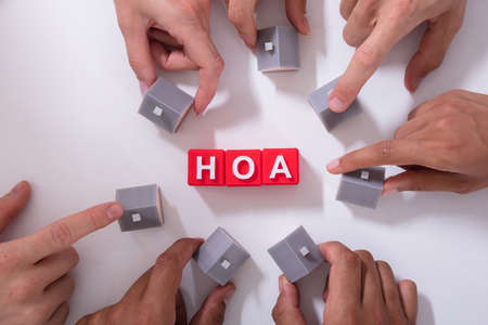 Homeowner Association Blocks Surrounded By People Holding House Model On White Surface