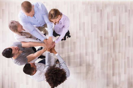 High Angle View Of Team Stacking Their Hands