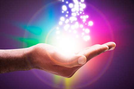 Luces incandescentes que fluyen de una mano abierta contra el telón de fondo del círculo colorido