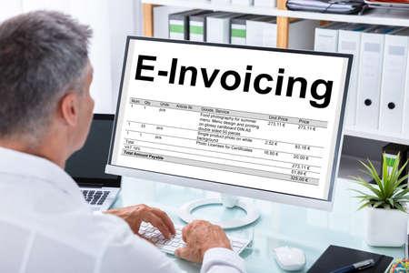 Mature Businessman Preparing E-invoicing Bill On Computer At Workplace Stock Photo