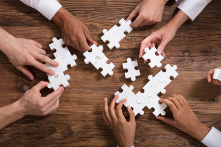 Businesspeople Solving White Jigsaw Puzzle Together On Wooden Desk