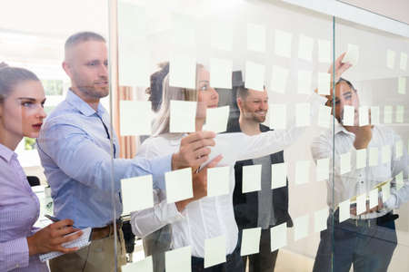 Group Of Young Businesspeople Sticking Adhesive Notes On Transparent Glass Wall In Office 版權商用圖片