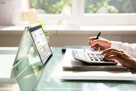 Close-up van de hand die van een zakenman factuur berekent die calculator gebruiken Stockfoto