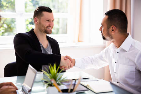 Two Happy Young Businessmen Shaking Hands In Office