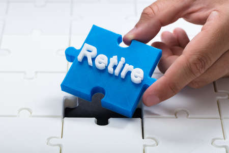 Close-up of a person placing last blue retire piece into jigsaw puzzle