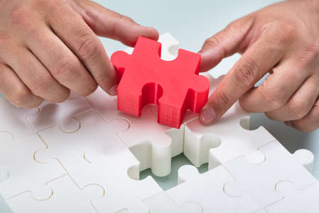 Close-up of a Businessmans hand connecting red piece into white jigsaw puzzles