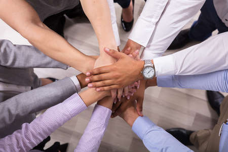 Elevated View Of Businesspeople Stacking Hands Over Each Other Stock Photo