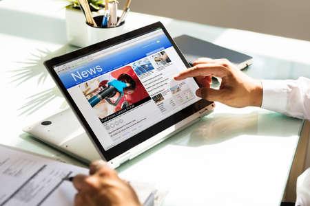 Businessmans hand checking online news on laptop over reflective desk