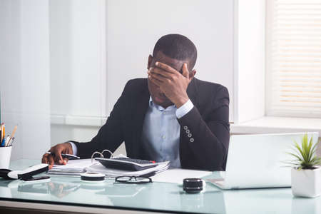 Close-up Of Worried Young Businessman Looking At Calculator On The Invoice In The Office Stock Photo