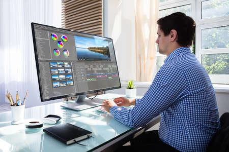 Junger männlicher Redakteur, der Video am Computer am Arbeitsplatz bearbeitet