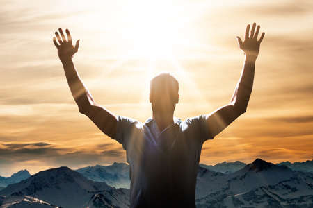 Man Raising His Arm In Front Of Mountain Landscape