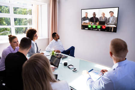 Group Of Skillful Businesspeople Video Conferencing In Boardroom Stock Photo