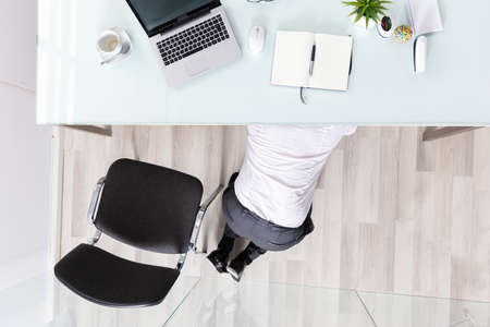 High Angle View Of A Businessman Hiding Under Desk In Office