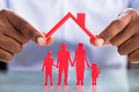 Close-up Of Businessmans Hand Holding Roof Over The Red Family Standing On Reflective Desk Stock Photo