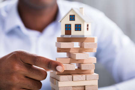 Close-up Of A Person Hand Holding Blocks With Miniature House