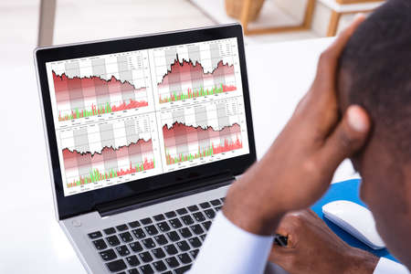 Close-up Of Worried Businessman With Graph Chart On The Laptop Screen At Workplace