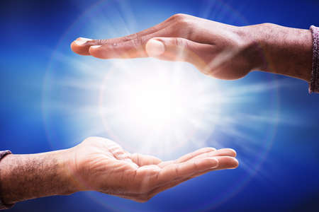 Males Hand Collecting Glowing Sunlight Flare Against Blue Background Stock Photo