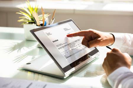 Gros plan, de, a, homme affaires, main, examiner, facture, sur, ordinateur portable