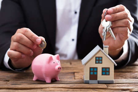 Businesspersons hand holding coin and key over piggybank and house on wooden desk Stock Photo