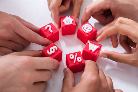 Close-up Of People Holding Red Cubic Blocks With Vivid Icons On White Surface