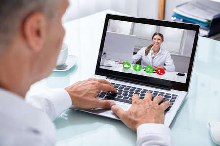 Businessmans Hand Videoconferencing With Happy Female Doctor On Laptop Stock Photo