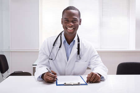 Close-up Of A Smiling Male Doctor With Clipboard And Pen Sitting In Clinic Stock Photo