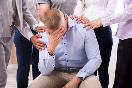 Gruppe von Menschen, die verärgerten Mann trösten, der auf Stuhl sitzt