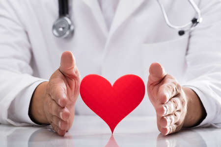 Doctors hand protecting red heart on desk