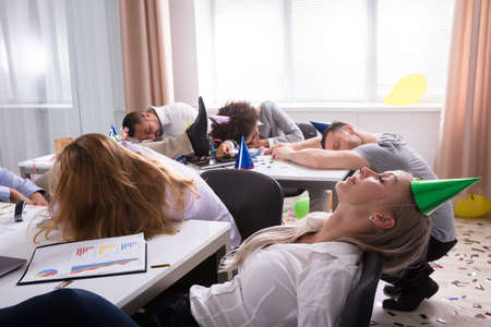 Group Of Businesspeople Sleeping In Office After New Year Party Stock Photo