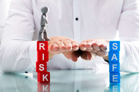 Close-up of a persons hand assisting human figure while moving from risk to safe blocks Stock Photo