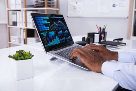 Close-up Of Businessman Analyzing Graph On Laptop At Workplace In The Office Stock Photo