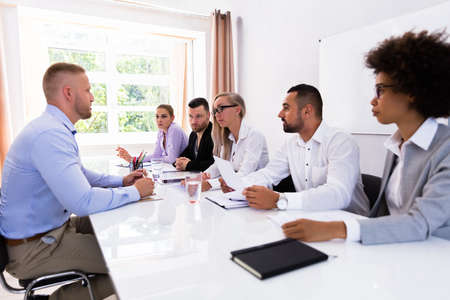 Young Man Sitting At Interview Meeting At Office Stock Photo