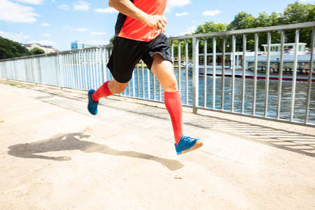 Low Section View Of A Man Running On Sidewalk At Morning Stock Photo