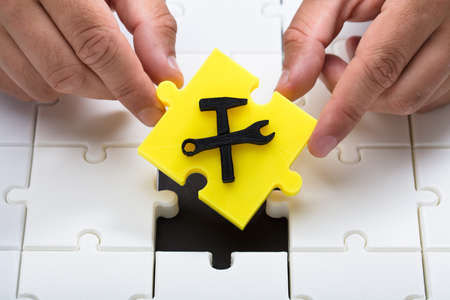 Human hand placing last yellow piece with under construction icon into jigsaw puzzles
