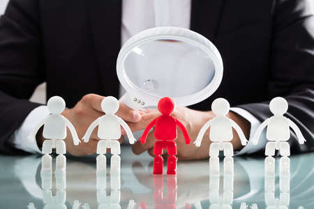 Businesspersons hand looking at red human figure through magnifying glass on reflective desk