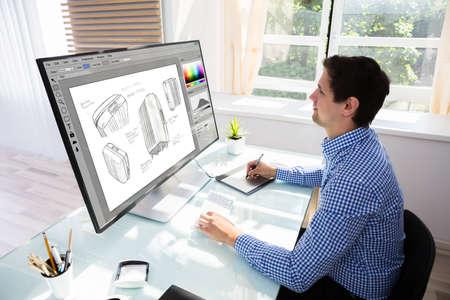 Vista lateral de un joven diseñador masculino maleta de dibujo en computadora con tableta gráfica