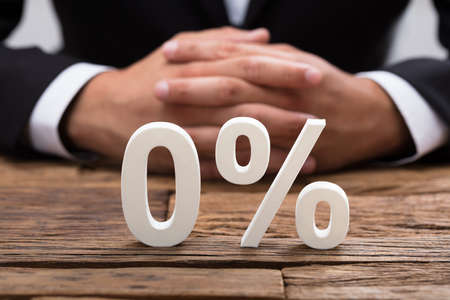 White zero percentage symbol in front of businesspersons hand