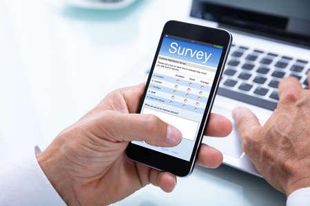 Close-up Of A Businessmans Hand Filling Online Survey Form On Smartphone