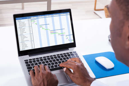 Close-up Of A Businessman Working With Gantt Chart On Laptop Over The Desk Imagens